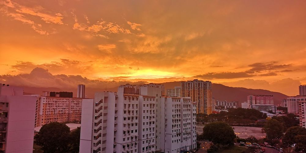 Buildings against dramatic sky during sunset