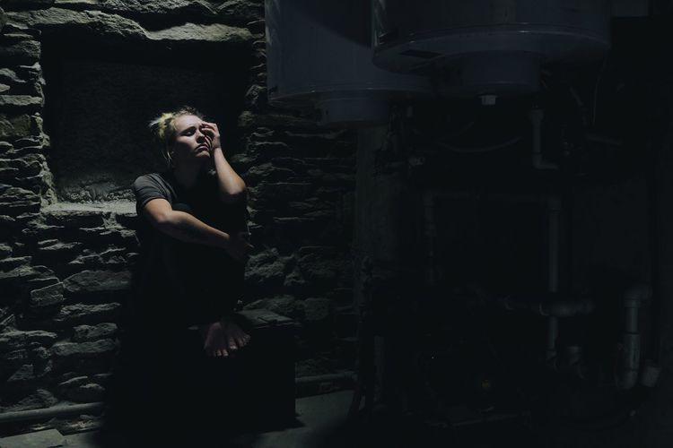 Portrait of depressed woman in basement