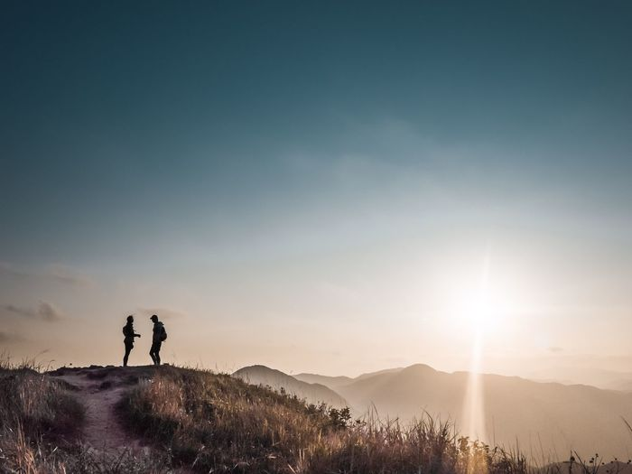 Silhouette people on mountain against sky during sunset
