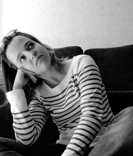 Thoughtful Young Woman Looking Up While Sitting On Sofa