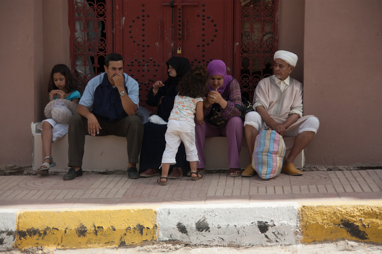 sitting, real people, full length, casual clothing, mature men, lifestyles, medium group of people, mature women, boys, father, son, girls, men, outdoors, day, togetherness, young women, young adult, architecture
