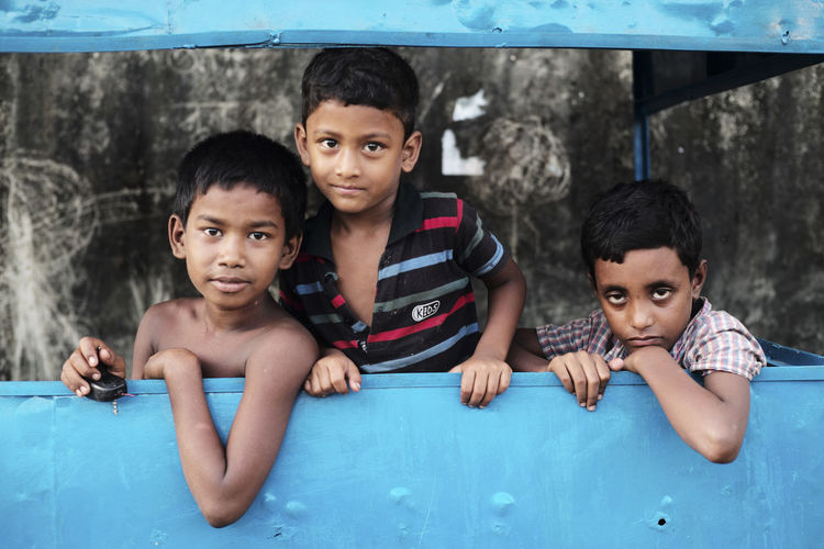Three of my neighbours from the nearby slum, posing inside a makeshift caravan. Adult Black Hair Bonding Boys Child Childhood Close-up Day Elementary Age Father Friendship Headshot Leisure Activity Lifestyles Looking At Camera Outdoors People Portrait Real People Sibling Smiling Son Streetphotography Togetherness Young Adult