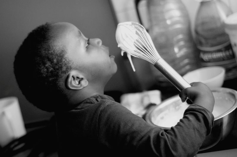 Side view of african boy holding wire whisk