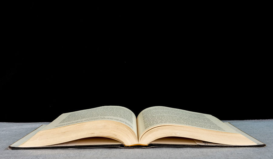 Open book on table against black background