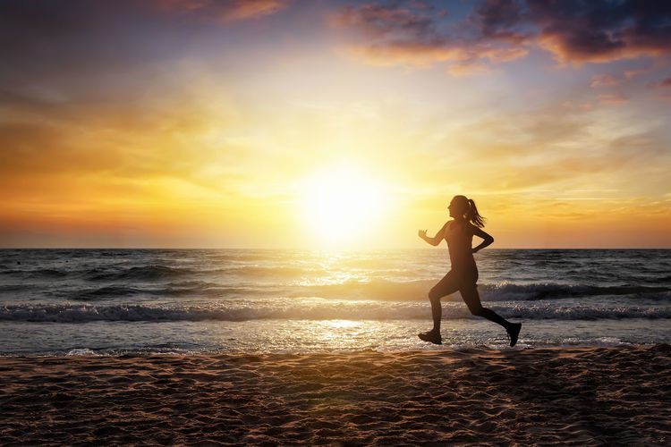 Woman running on the beach at sunset time in summer Sunset Sea Beach Water One Person Sky Lifestyles Leisure Activity Women Horizon Over Water Cloud - Sky Scenics - Nature Real People Running Workout Marathon Training Summer Exercise Exercising Alone Freedom Jogging Motion Athlete