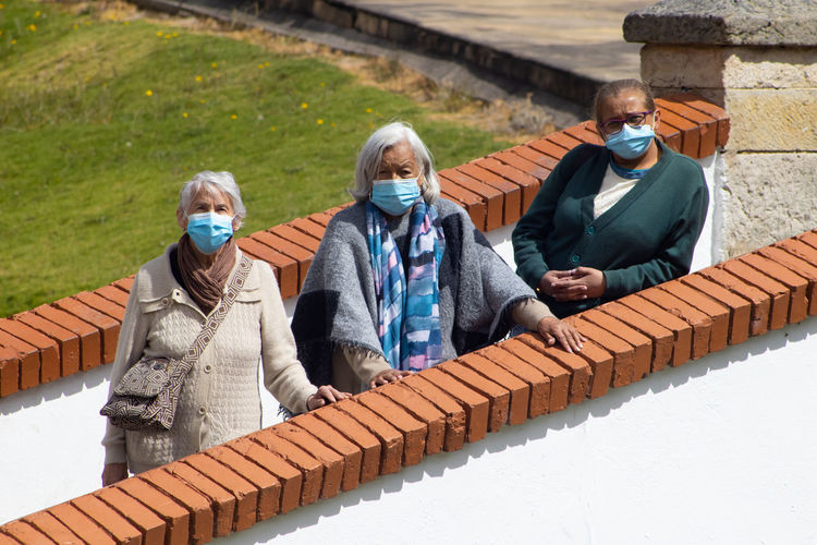 Senior people wearing mask standing by brick wall outdoors