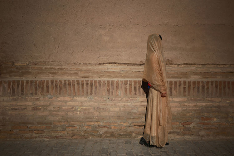 Side view of woman wearing traditional clothing standing against wall