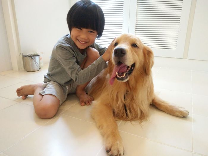Portrait Of Smiling Boy Petting Golden Retriever On Floor At Home
