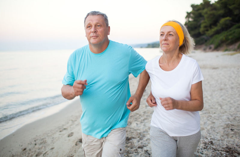 Mature couple jogging on shore at beach