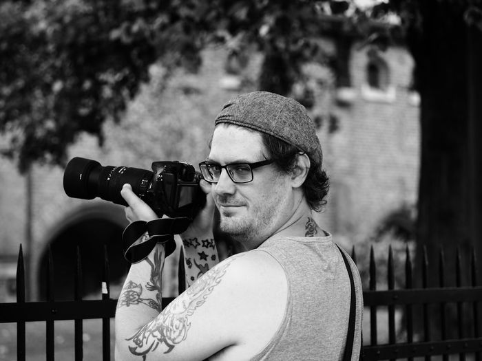 Portrait of hipster photographing through camera by fence at park