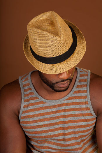 Handsome fit African American Man in a casual outfit with a brown background African American Casual Hat Macho Black Man Brown Casual Clothing Front View Good Looking Man Handsome Indoors  Lifestyles One Person Straw Hat Tank Top Young Men