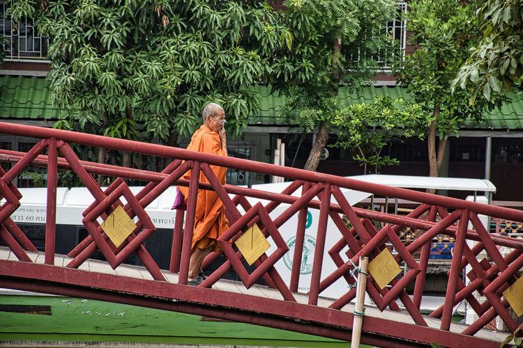 Full length of woman sitting on railing against trees