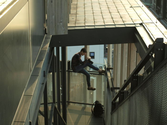 High angle view of mid adult woman photographing while sitting on railing