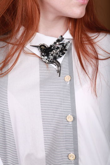 Midsection of woman wearing brooch on dress