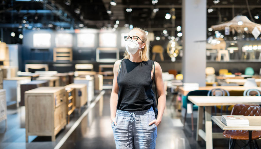 Woman wearing flu mask standing at store