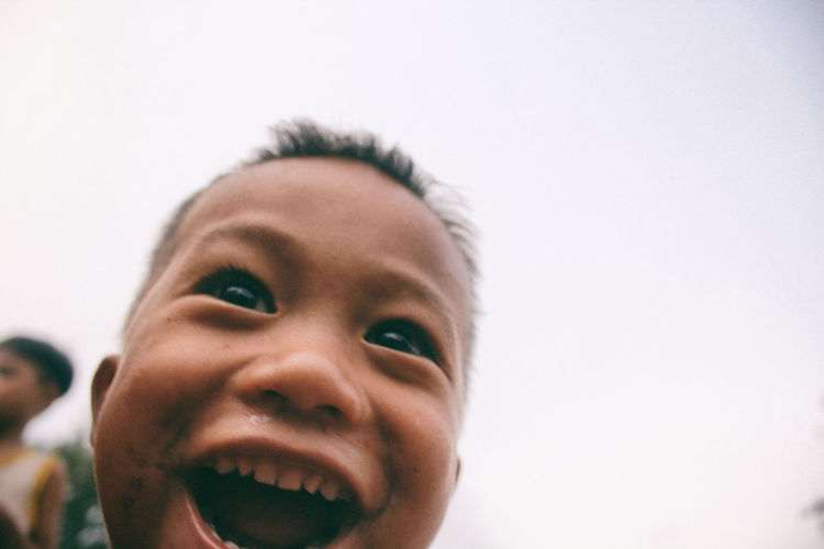 Portrait of smiling boy against clear sky