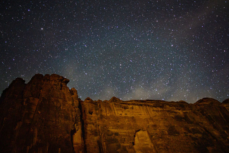 Scenic view of rock formations against sky at night