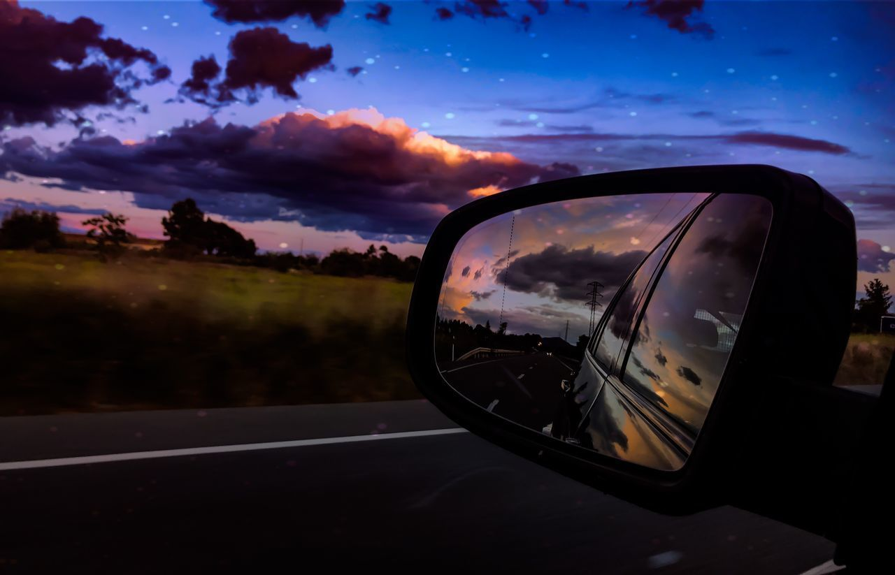 sky, cloud - sky, mode of transportation, transportation, car, sunset, land vehicle, side-view mirror, reflection, motor vehicle, road, nature, no people, glass - material, mirror, outdoors, close-up, orange color, city, dusk, road trip, vehicle mirror