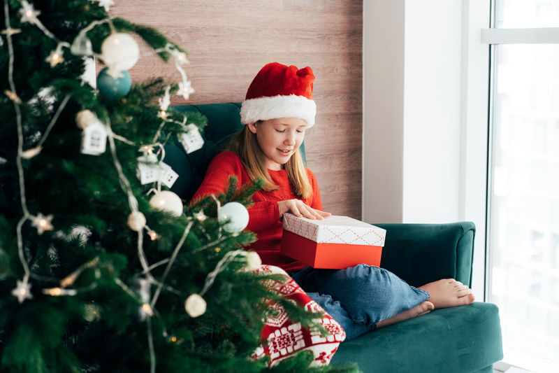 Full length of young woman sitting in christmas tree