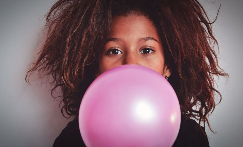 Portrait of woman with pink balloons