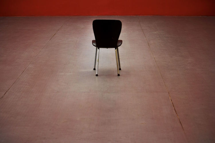 Empty chair on floor against red wall