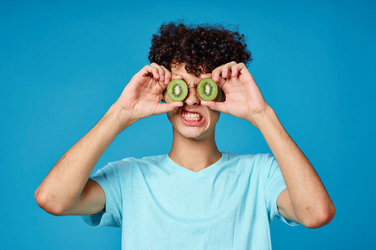 Portrait of man holding kiwi slices standing against blue wall