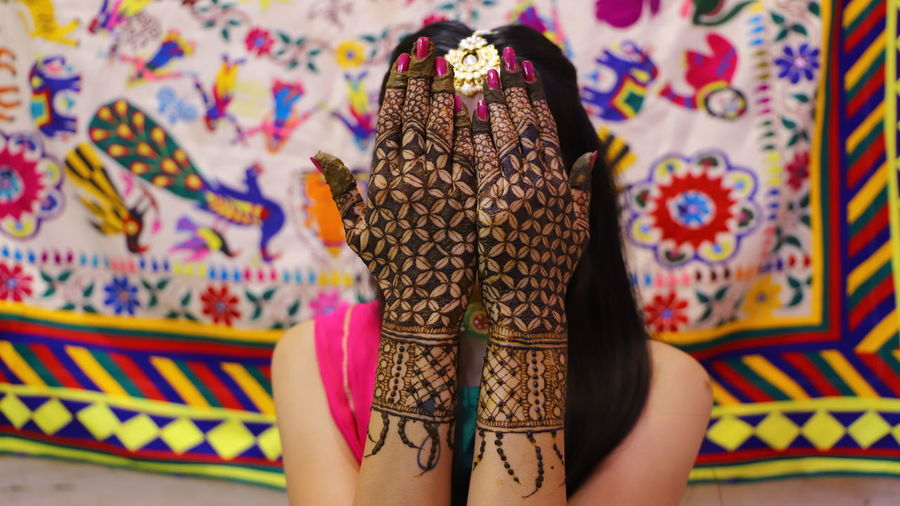 Young woman with henna tattoo during haldi ceremony