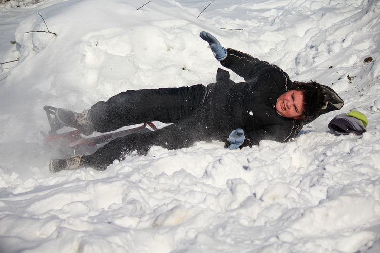 High angle view of boy falling in snow