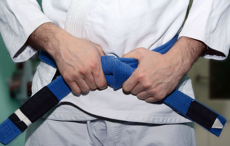 Midsection of man wearing belt while practicing karate