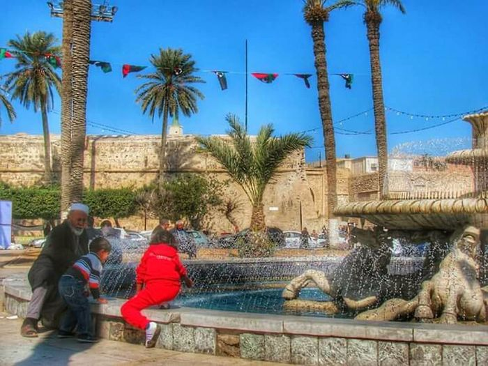 Children playing near the fountain next to their father,Martyrs Square ©Hiba Shalabi People Sitting Lifestreet EyeEm Libyan Photography هبة_شلابي Hibashalabi Tripoli Libya Outdoors The Street Photographer - 2017 EyeEm Awards Everydaymiddleeast Africa Children Cityscape City View  City Life Oldcity Fountain Love Lifescape Eyemphotography The Street Photographer - 2017 EyeEm Awards Place Of Heart The Street Photographer - 2017 EyeEm Awards Live For The Story