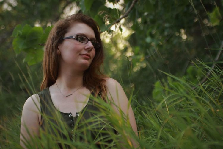 Thoughtful young woman wearing eyeglasses while looking away by grass