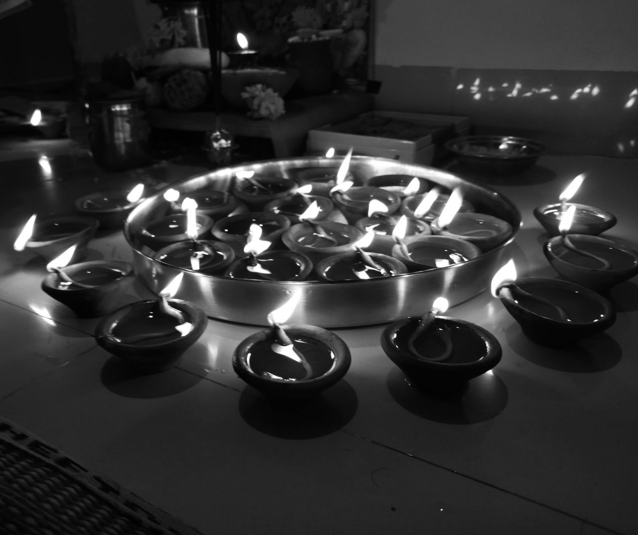 burning, flame, fire, candle, illuminated, glowing, fire - natural phenomenon, heat - temperature, no people, indoors, high angle view, tea light, religion, lighting equipment, decoration, large group of objects, nature, spirituality, belief, built structure, flooring, electric lamp