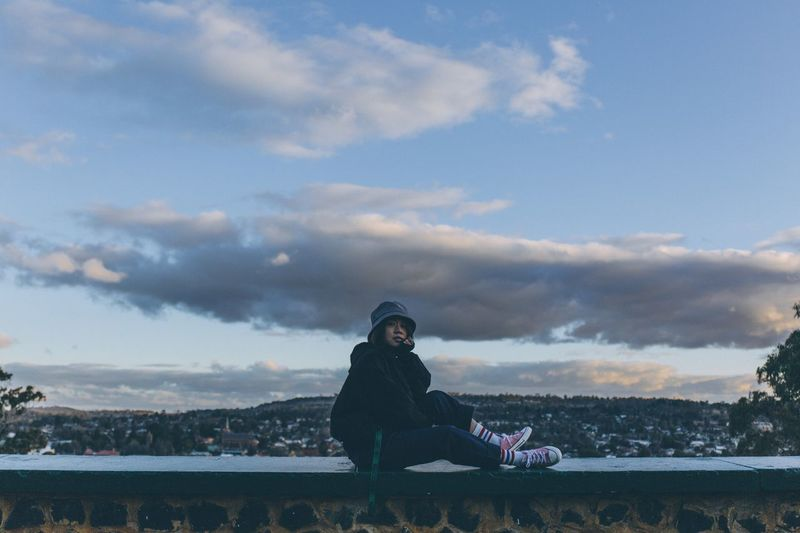 Portrait of woman sitting on wall against sky