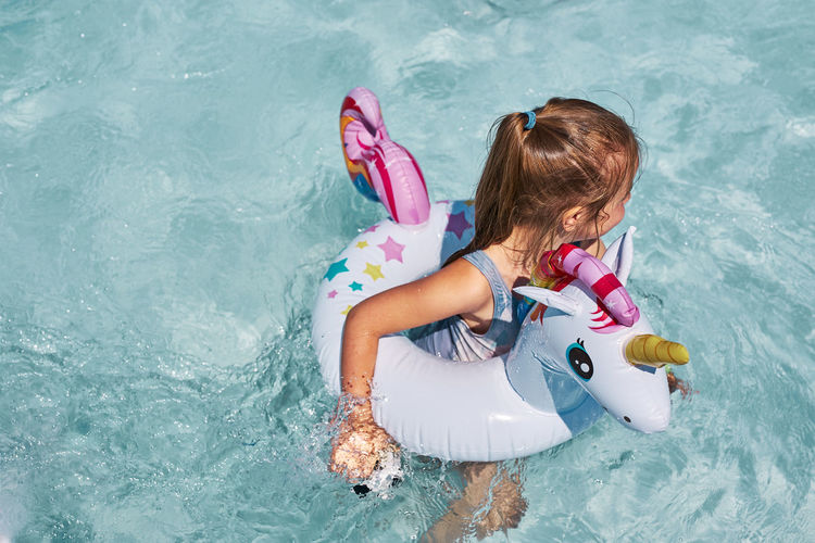 Little girl playing in a swimming pool with inflatable rubber ring toy in the shape of unicorn
