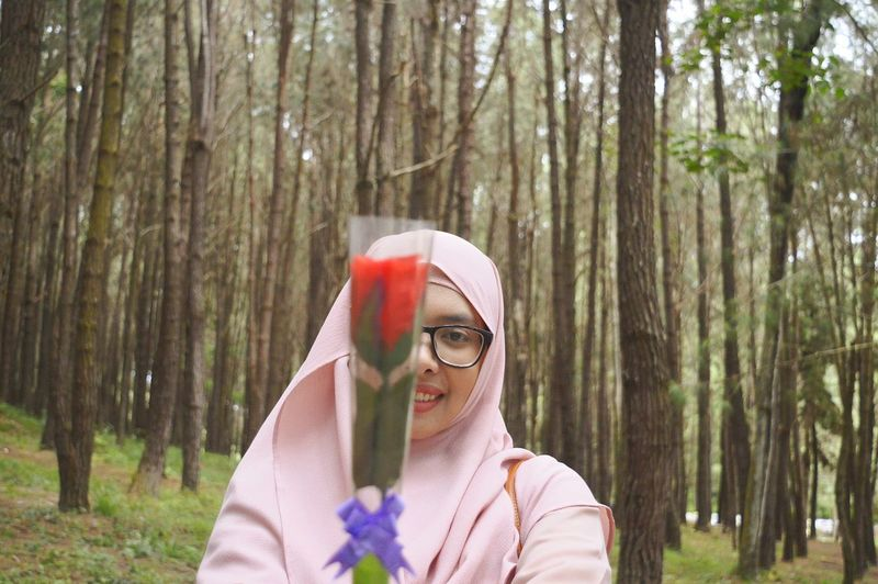 Portrait of young woman holding flower in forest