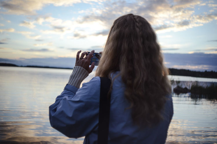 Rear view of woman photographing lake through smart phone at sunset