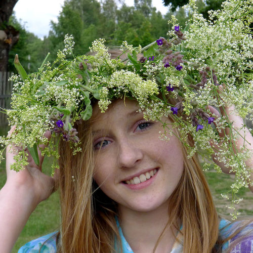 Portrait of a smiling young woman against white flowering plants