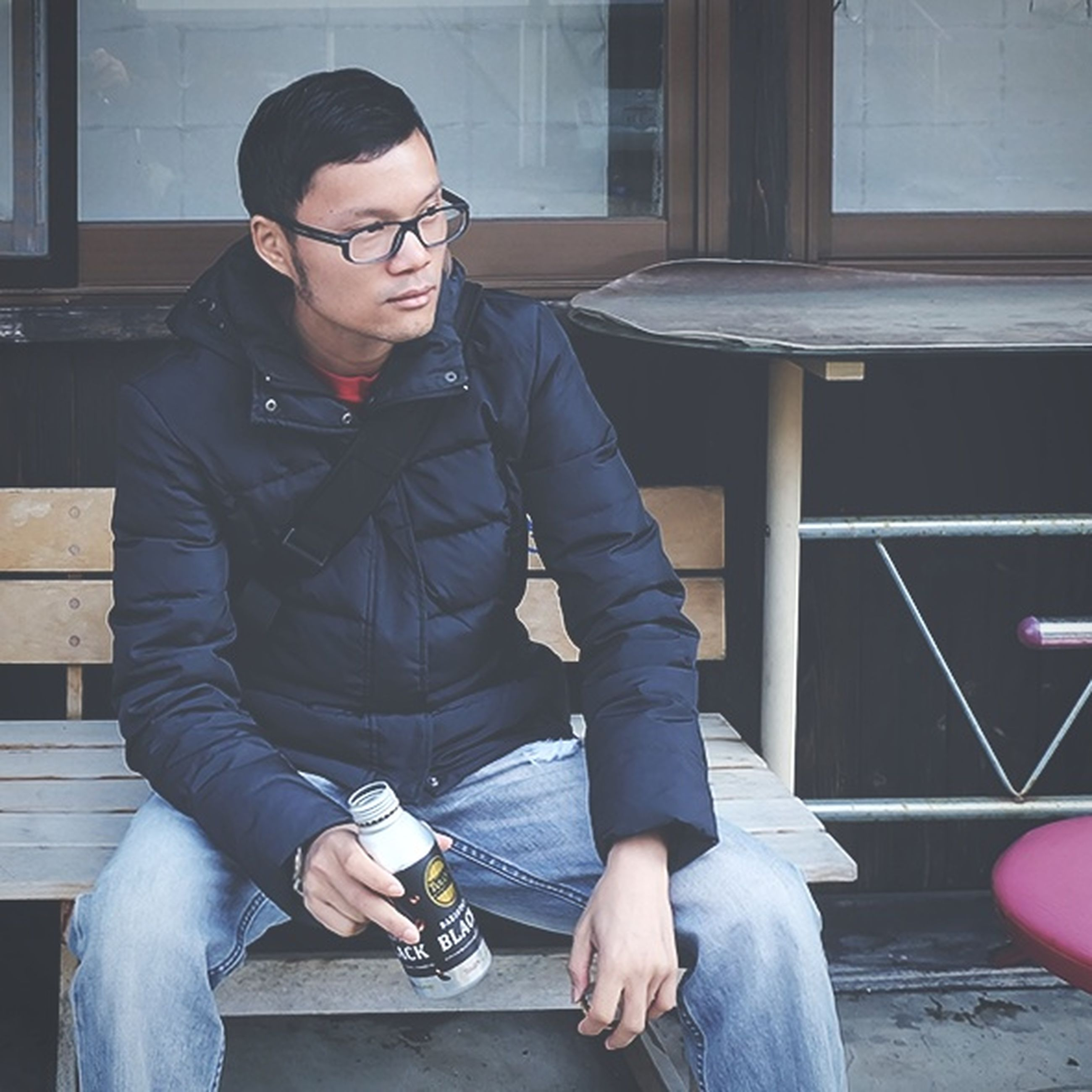 eyeglasses, sitting, one person, real people, three quarter length, young adult, casual clothing, front view, glasses, jacket, lifestyles, leisure activity, day, young men, relaxation, young women, portrait, outdoors, people