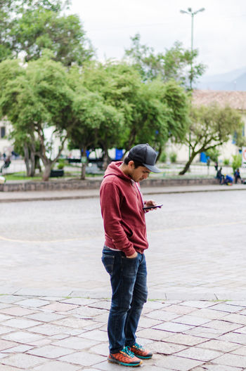Man using phone while standing on footpath