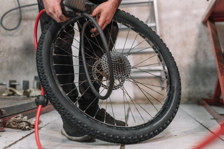 Low section of mechanic repairing wheel