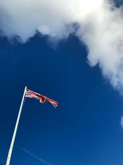 Low angle view of british flag against blue sky