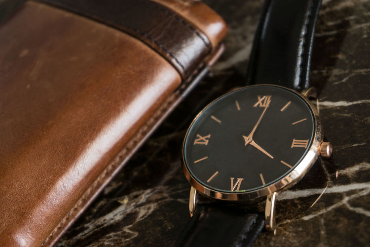 Close-up of wristwatch by wallet on table