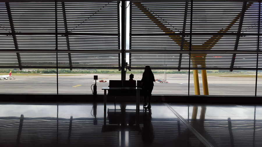 Silhouette people sitting at airport