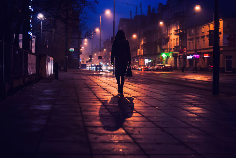 Rear View Of Silhouette Woman Walking On Footpath In City At Night