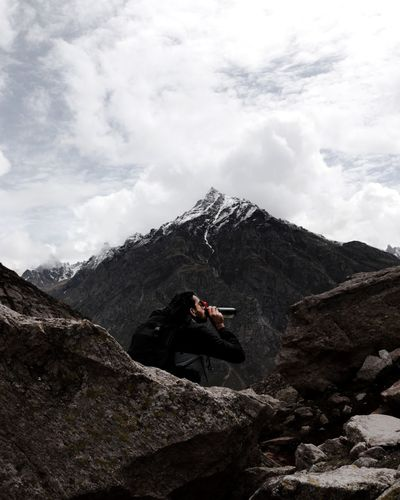 Hiker drinking water sitting on rocky mountain against sky