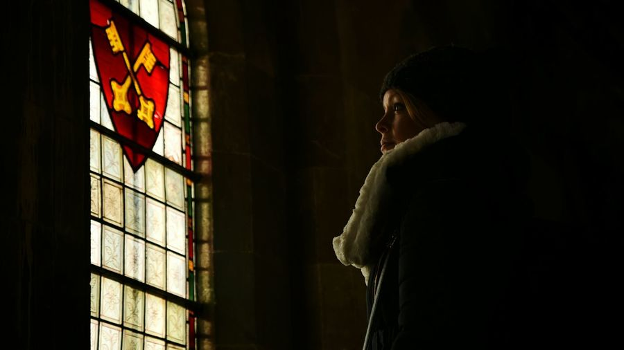 Side view of young woman looking away against emblem on window