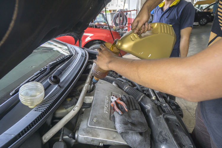 Midsection Of Mechanic Pouring Oil In Container