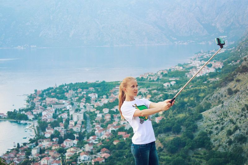 High angle view of woman taking selfie against town by sea