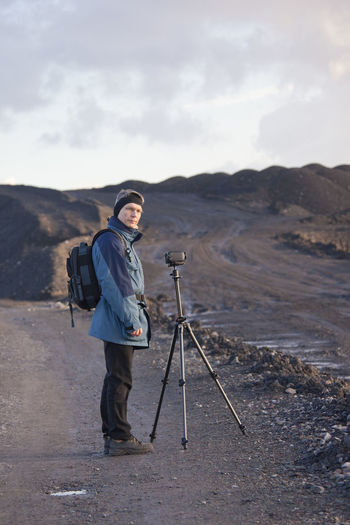Portrait of man standing by digital video camera with tripod by field against sky