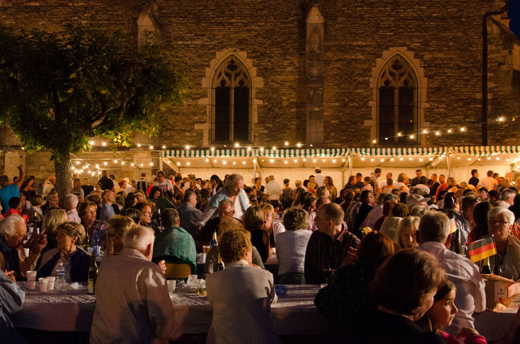 Audience Crowd Large Group Of People Group Of People Architecture Real People Men Built Structure Place Of Worship Sitting Women Illuminated Building Exterior Adult Young Adult Travel Destinations History Night Religion Party - Social Event 14 Juillet Feast Banquet Urban Scene Exterior Friend Couple Street Scene